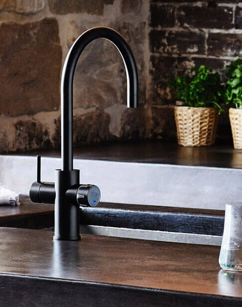 Black Celsius Arc Tap in a rustic kitchen